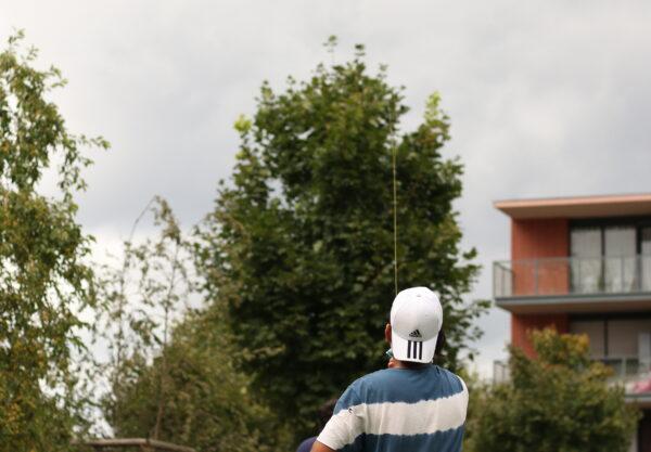 Un jeune du quartier profite de la météo pour tester un cerf volant fabriqué à la main